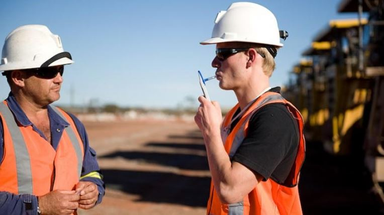 A Construction worker using breathalyser